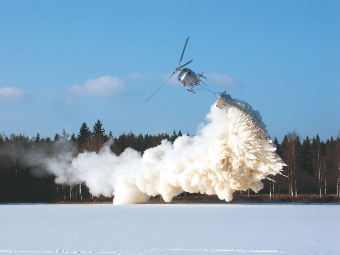A photograph showing powdered limestone sprayed from a helicopter to reduce the acidity in a lake in Sweden.